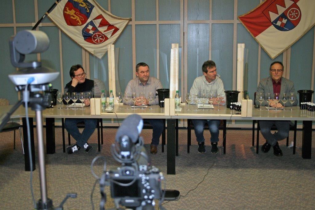 Vier Männer sitzen hinter einem Tisch mit Weingläsern. Im Vordergrund ist eine Kamera aufgebaut.