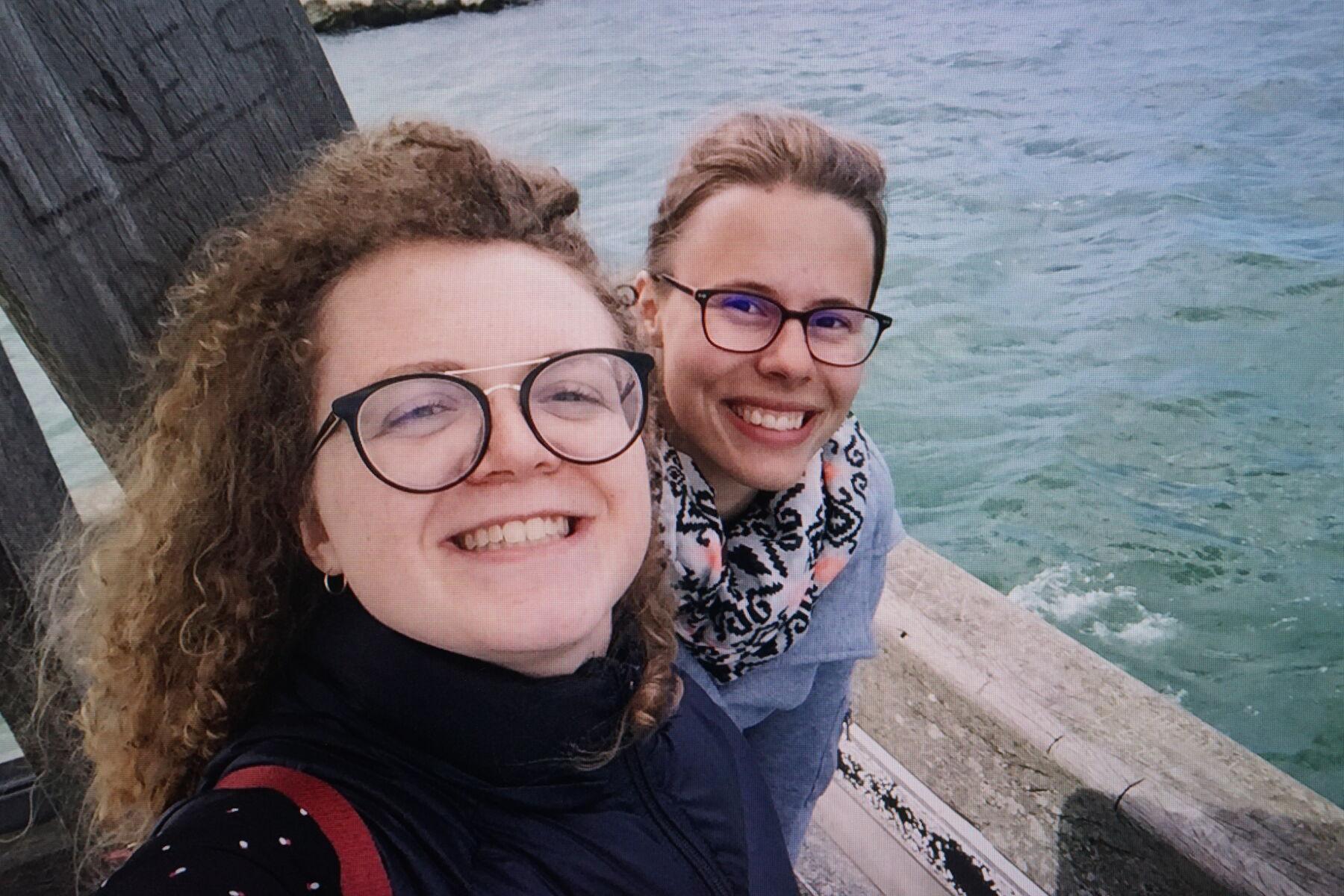Zwei Mädchen stehen am Meeresufer.