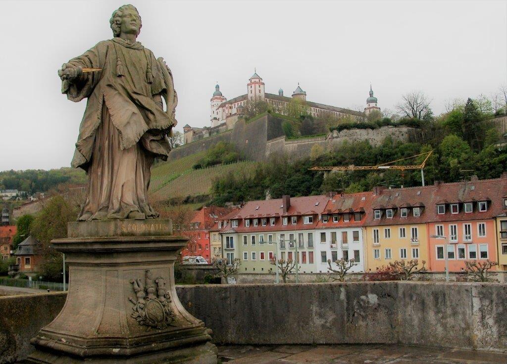 Eine steinerne Statue auf einer Brücke. Im Hintergrund ist die Festung Marienberg zu sehen.