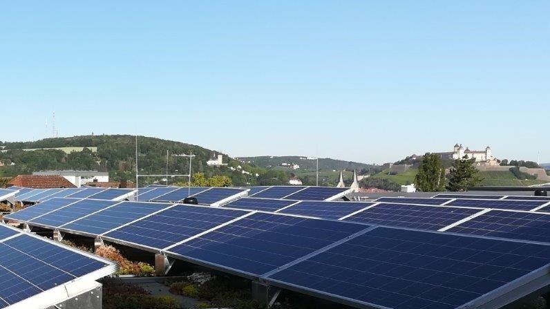 Photovoltaikanlage auf einem Dach. Im Hintergrund sieht man die Festung Marienberg.