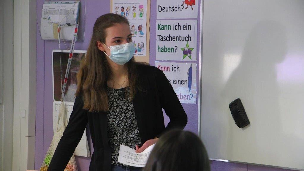 Eine junge Frau mit Mundschutz unterrichtet eine Klasse.