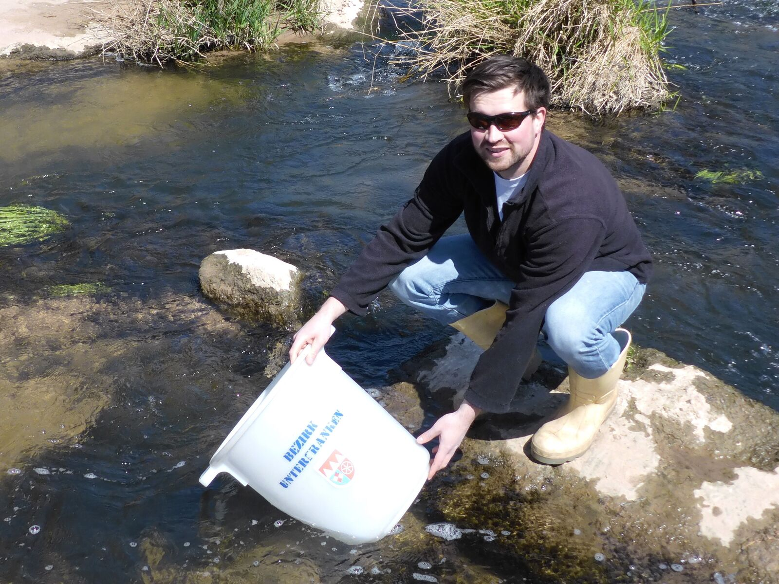 Mann lässt Fische ins Gewässer
