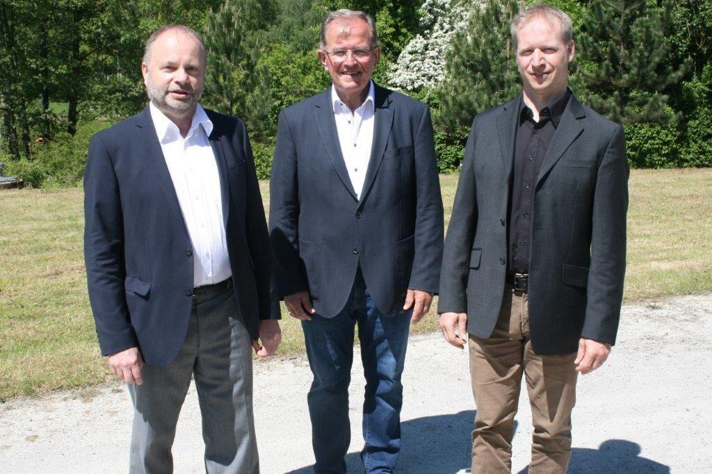 Drei Männer stehen im Freien.