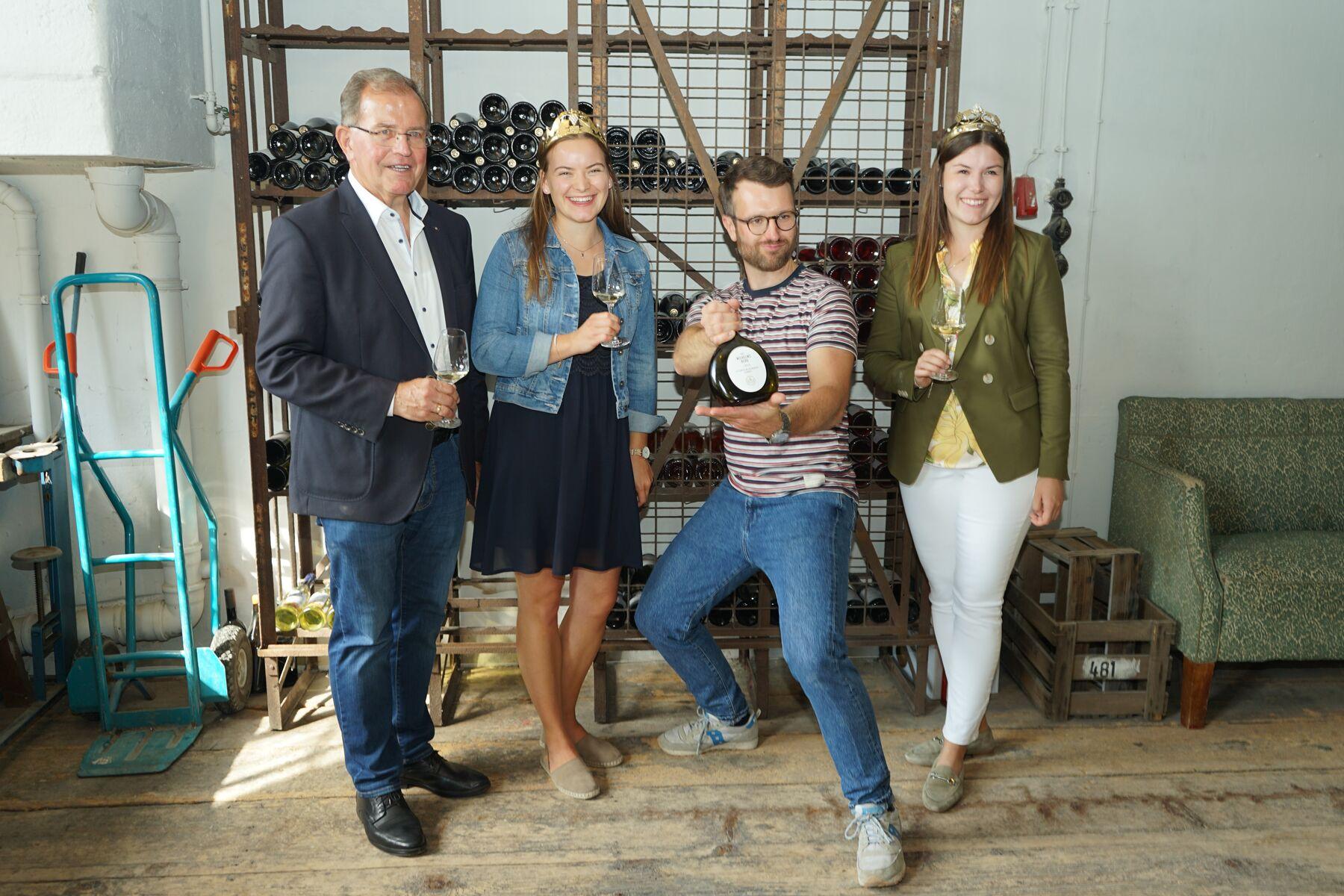 Bezirkstagspräsident Dotzel posiert mit drei Personen vor einem Weinregal