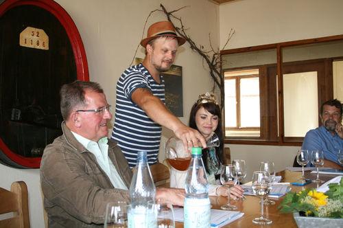 Michael Völker schenkt Bezirkstagspräsident Erwin Dotzel und der Fränkischen Weinkönigin Kristin Langmann seinen Naturwein ein.