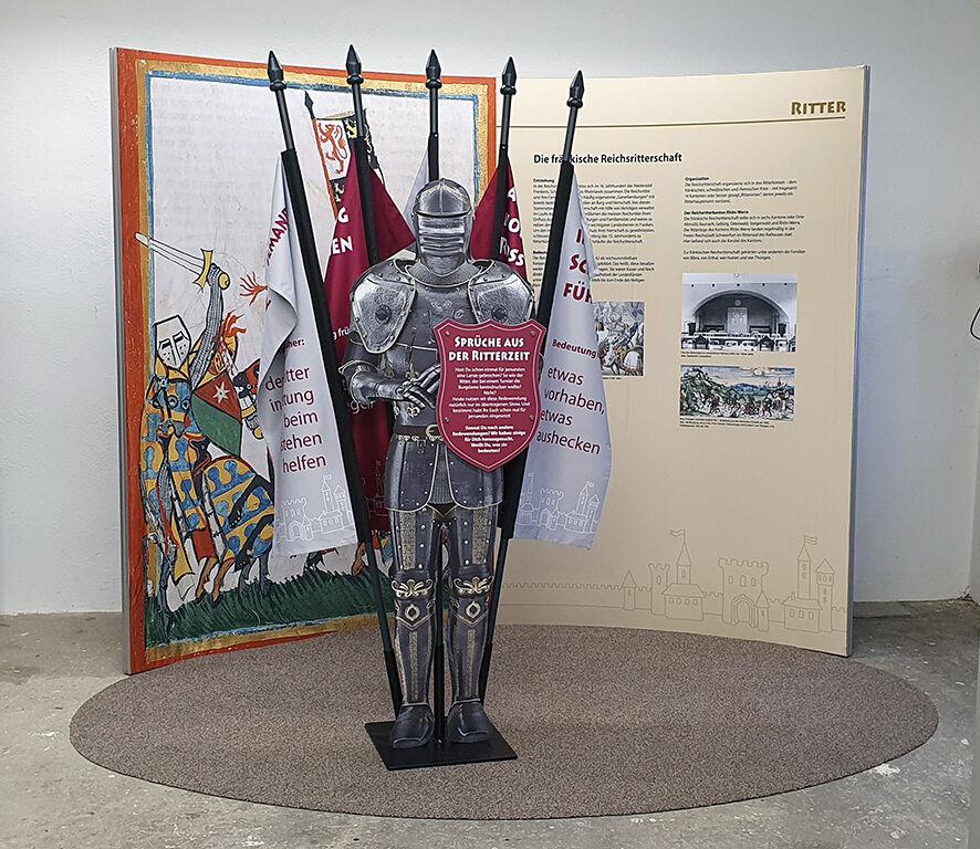 Ausstellungseinheit mit einer Ritterrüstung und Fahnen.