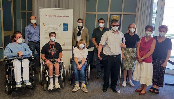 Ein Gruppe von Menschen, darunter drei Personen im Rollstuhl und eine Person mit Blindenstock stehen vor einer Texttafel.